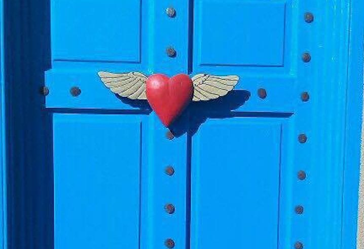 Life insurance and taxes | Photo of a red heart with wings on a blue door | Photo by Rita Pouppirt